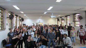 Imagem do coordenador do curso de Libras na Secretaria de Estado dos Direitos da Pessoa com Deficiência de São Paulo, a gerente do Centro de Tecnologia e Inovação e dos alunos do curso de Libras no anfiteatro do Centro de Tecnologia e Inovação. Ambos fazem o sinal de eu te amo em Libras.