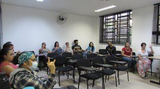 Imagem da sala de aula. Alunos sentados em cadeiras fazendo sinais de Libras.