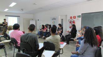 Imagem da sala de aula. Alunos sentados em cadeiras, posicionadas em formato da letra U, fazendo sinais de Libras.