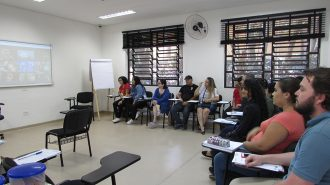 Imagem da sala de aula. Alunos sentados em cadeiras olhando para a lousa interativa no fundo da sala.