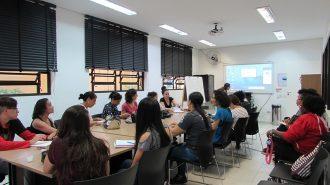 Imagem da sala de aula. Alunos sentados em cadeiras, próximos de uma mesa grande. Ao fundo, a professora olhando para o computador, ao lado da lousa interativa.