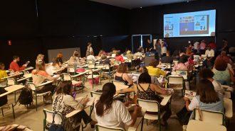 Imagem da sala de aula. Alunos sentados em cadeiras folheando revistas e alguns alunos em pé, no fundo da sala.