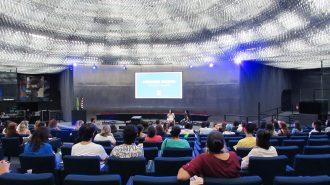 Imagem do auditório da Secretaria de Estado dos Direitos da Pessoa com Deficiência de São Paulo. Em primeiro plano, alunos sentados em poltronas. Ao fundo, no palco do auditório, a Secretária Célia Leão e a gerente do Programa Moda Inclusiva Izabelle Palma.
