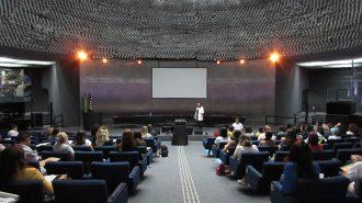 Imagem do auditório da Secretaria de Estado dos Direitos da Pessoa com Deficiência de São Paulo. Em primeiro plano, alunos sentados em poltronas. Ao fundo, no palco do auditório, a professora em pé.