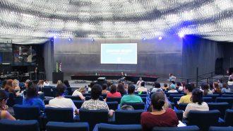 Imagem do auditório da Secretaria de Estado dos Direitos da Pessoa com Deficiência de São Paulo. Em primeiro plano, alunos sentados em poltronas. Ao fundo, no palco do auditório, a gerente do Programa Moda Inclusiva, Izabelle Palma.