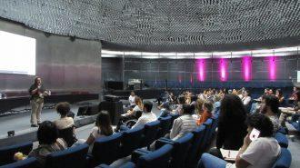 Imagem dos alunos do curso de Moda Inclusiva – Módulo Criação sentados em poltronas e da professora, em pé, falando ao microfone, no palco do auditório da Secretaria de Estado dos Direitos da Pessoa com Deficiência de São Paulo.