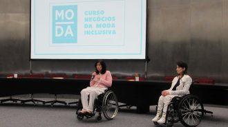 Imagem da Secretária Célia Leão, falando ao microfone, ao lado da gerente do Programa Moda Inclusiva Izabelle Palma, no palco do auditório da Secretaria de Estado dos Direitos da Pessoa com Deficiência de São Paulo.
