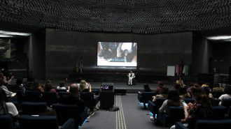 Imagem do auditório da Secretaria de Estado dos Direitos da Pessoa com Deficiência de São Paulo. Em primeiro plano, alunos sentados em poltronas. Ao fundo, no palco do auditório, a gerente do Programa Moda Inclusiva Izabelle Palma.