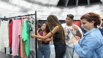 Imagem de alunos do curso de Moda Inclusiva – Módulo Negócios olhando looks inclusivos pendurados em uma arara.