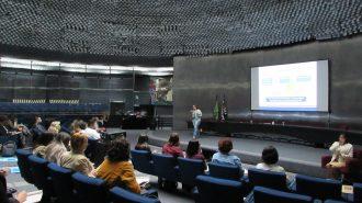 Imagem do auditório da Secretaria de Estado dos Direitos da Pessoa com Deficiência de São Paulo. Em primeiro plano, alunos sentados em poltronas. Ao fundo, no palco do auditório, a professora do curso.