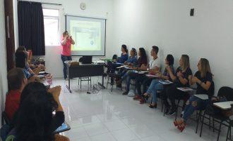 Foto da sala de aula. Em primeiro plano, alunos sentados em cadeiras. Ao fundo, a professora fazendo sinais em Libras.