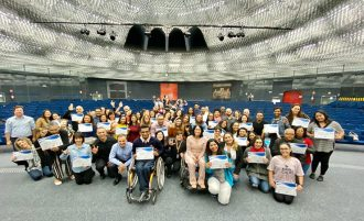 Secretária Célia Leão, assessores e alunos do curso de Libras no palco do auditório da Secretaria de Estado dos Direitos da Pessoa com Deficiência de São Paulo.