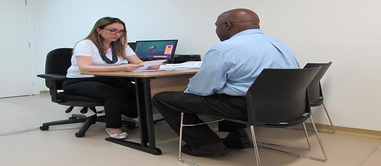 Imagem de uma assessora em inclusão entrevistando um candidato. Ambos estão sentados próximos a uma mesa. A assessora segura uma folha de sulfite.