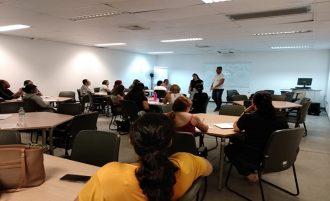 Em primeiro plano, alunos sentados em cadeiras. Ao fundo, o professor em pé, em frente à lousa.