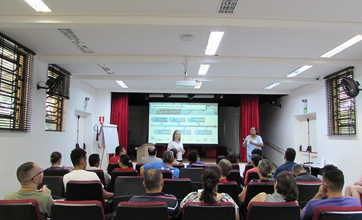 Foto do Auditório do Centro de Tecnologia e Inovação. Em primeiro plano, pessoas sentadas em poltronas. Ao fundo, a palestrante e a intérprete de Libras, em pé.