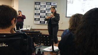 Em primeiro plano, participantes do evento sentados. Ao fundo, a professora Andreia Miron falando ao microfone, em pé.
