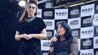Secretária Célia Leão falando ao microfone. Ao lado, a professora Andreia Miron.