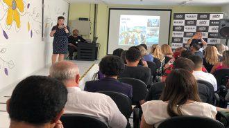 Em primeiro plano, participantes sentados em cadeiras. Ao fundo, no canto, a professora Andreia Miron e no outro lado o intérprete de Libras.