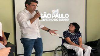 A Secretária Célia Leão e o Secretário Municipal de Desenvolvimento Social Carlos Mota falando ao microfone, no palco do auditório.