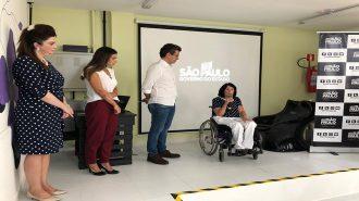 A Secretária Célia Leão ao microfone, o Secretário Municipal de Desenvolvimento Social Carlos Mota, a professora Andreia Miron e outra participante no palco do auditório.