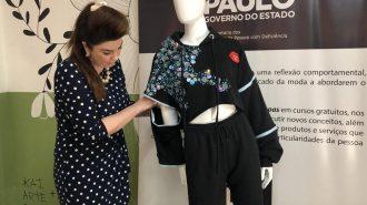 A professora Andreia Miron segurando o look inclusivo de um manequim.