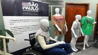 Em primeiro plano, manequins com looks inclusivos. Ao fundo, um banner com informações sobre o Programa Moda Inclusiva.