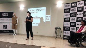 A Professora Andreia Miron falando ao microfone e a Secretária Célia Leão ao lado no palco do auditório.
