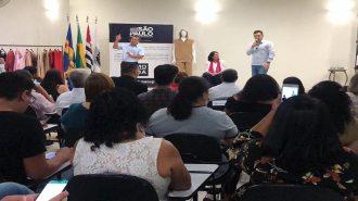Em primeiro plano, participantes da aula aberta de Moda Inclusiva. Ao fundo, o Prefeito Vinicius de Castro, a Secretária Célia Leão e o intérprete no palco do auditório.