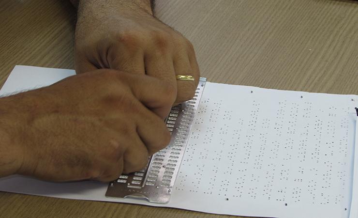 Duas mãos utilizando a reglete para escrever em Braille