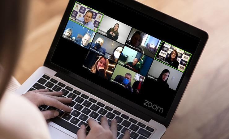 Card ilustrativo com foto de pessoa segurando notebook no colo, na tela, transmissão do evento virtual, dez janelas com pessoas participantes.