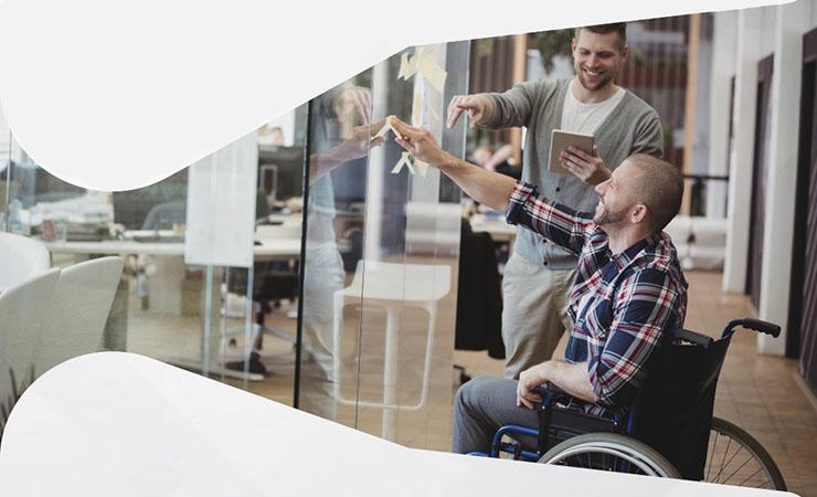 Foto de dois homens em ambiente corporativo, um deles utiliza cadeira de rodas.